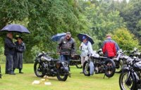 In the rain. Centre is Howard Wilcox's 1930 680 OHV with Kurt Haries looking on.  Under the umbrella can be seen Heather Wadsworth